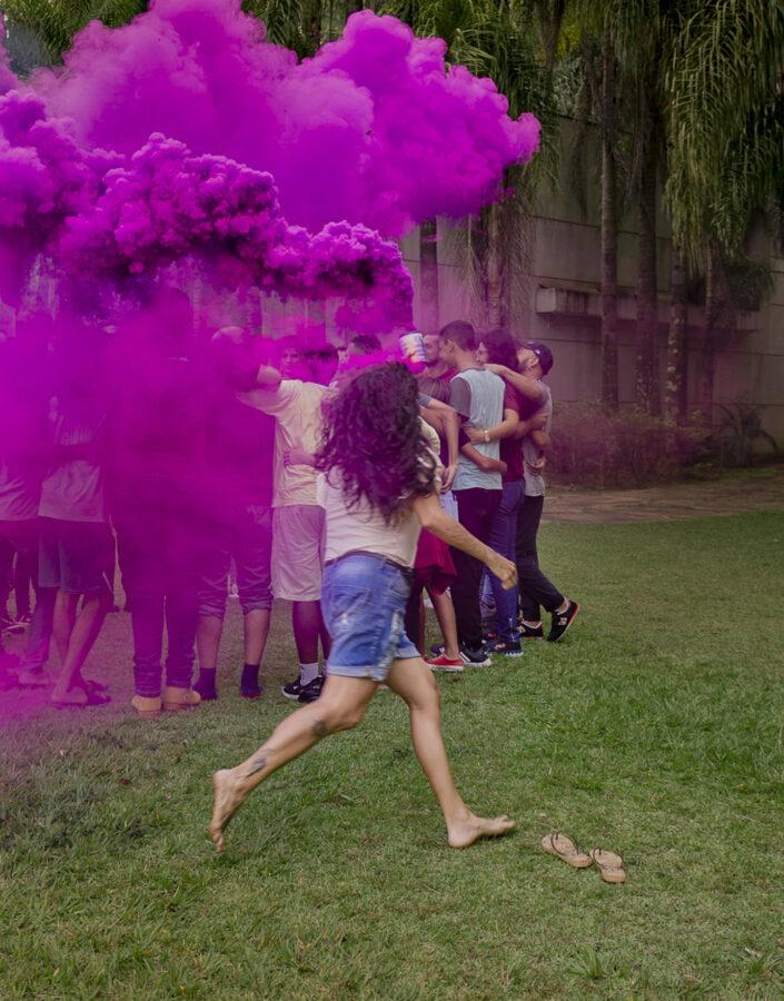 Educativo Inhotim pessoa correndo com fumaça roxa